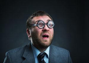 Surprised nerd businessman in glasses over grey
